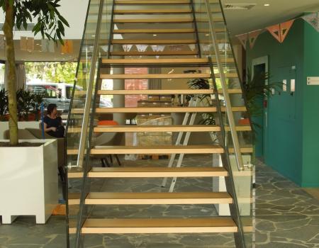 Gepoederlakte trap met treden in eik en een trapleuning-balustrade in glas met inox handgreep