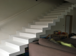 Moderne gesloten trap met vlakke trede in staal gepoederlakt