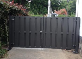Moderne gesloten poort opgebouwd uit  stalen buizen bekleed met beide zijden plaatstroken