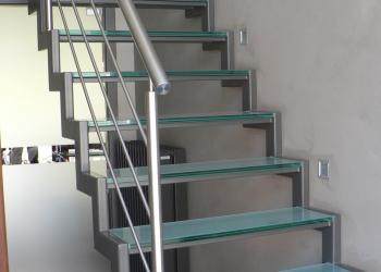 Gepoedercoate trap met kokers in trapvorm als trapwangen en treden in glas