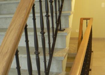Klassieke borstwering met verticale sierspijlen in gepoedercoat staal en houten handgreep