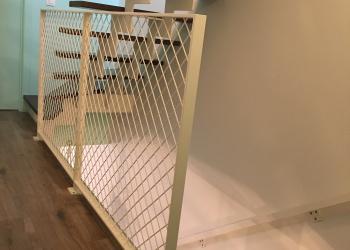 Gepoederlakte balustrade met kader in plat staal en vulling in schuin gelast draadnet met vierkante mazen
